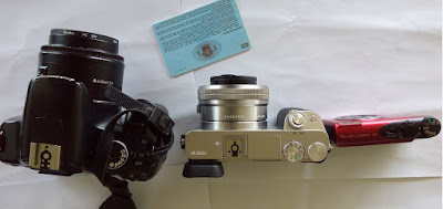 Foto Perbedaan ukuran antara kamera mirrorless dan kamera DSLR. Ada kamera DSLR Canon 450D, Kamera Sony A600