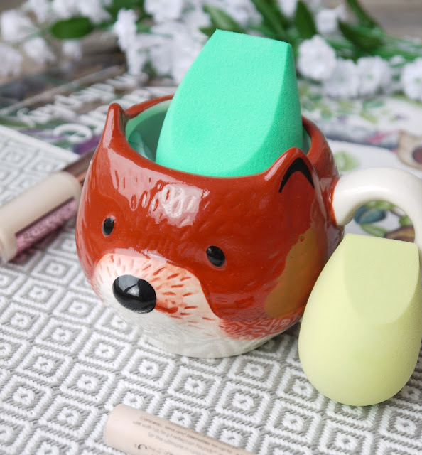 an emerald green ecotools sponge sat in a mug shaped and painted like a fox's face