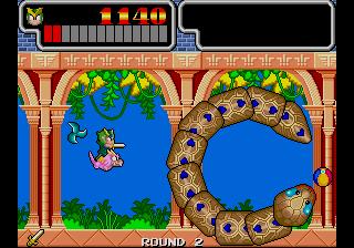 Captura de pantalla de Wonder Boy III: Monster Lair, Westone, 1988. La imagen muestra un jefe final con forma de serpiente con anillos bien armados. Nuestro protagonista, Wonder Boy, le dispara subido en un dragón rosa