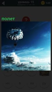 На парашюте осуществляется спуск аппарата в голубом небе