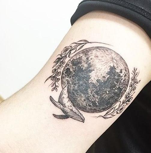 A lua funciona como a peça central deste tatuagem que casais aparentemente não-relacionadas de imagens, incluindo flores e uma baleia azul.
