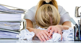 woman head down on crumpled papers next to notebooks and pens