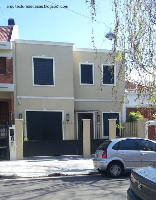 Fachada de residencia urbana contemporánea entre medianeras