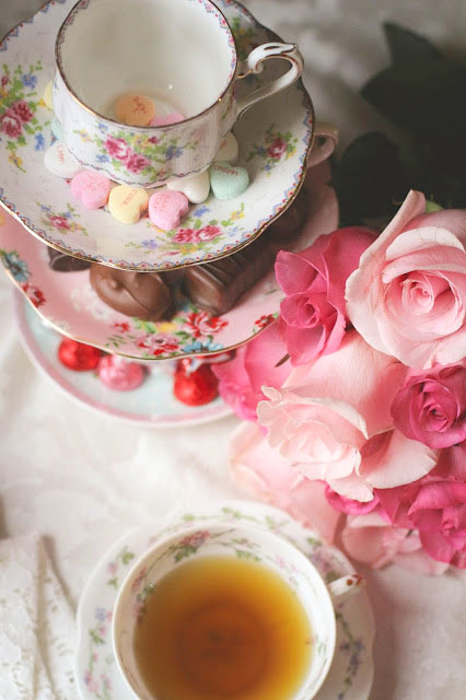 Tea, tea cups, heart candy charms and pink flowers on a table