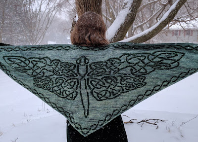 a person facing a snow covered scene, spreading their arms out to show a green and black shawl patterned like a dragonfly.