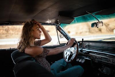 Chica rubia conduciendo un coche clásico en el desierto