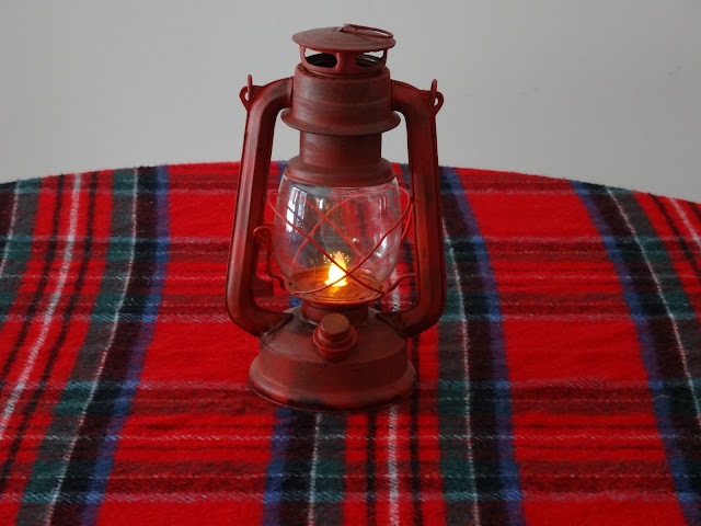 A red plaid scarf with faux lantern on the kitchen table.