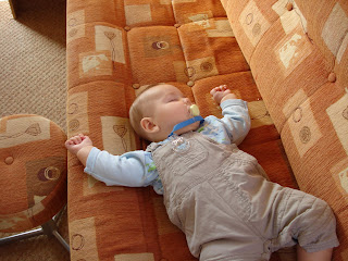 Baby Boy asleep on a Carivan sofa