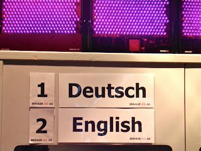 Deutsch/Englisch steht über Dolmetscherkabinen