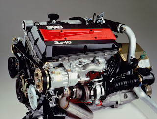 the serpentine belt and its various pulleys can be seen on the left side of  the engine in this photo