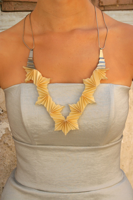 folded silver and ivory paper necklace on model