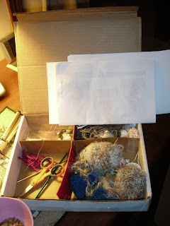 My softie box with all the various supplies needed except the yarn; very handy to keep all the little parts in the same place. The papers you see are all the free patterns I've been trying, also a handy place to keep my needles :)