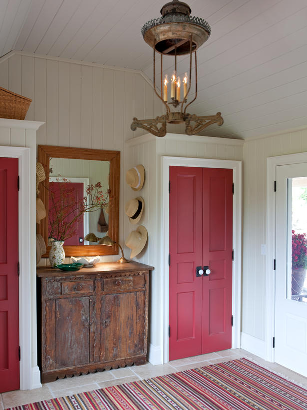 Gorgeous cherry red vintage closet doors in entry of Sarah Richardson farmhouse with beadboard ceiling