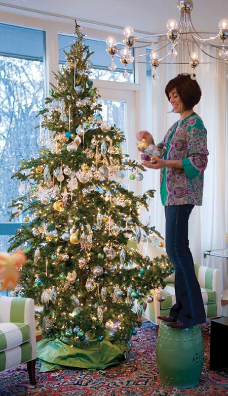 Sarah Richardson standing on ceramic stool decorating Christmas tree