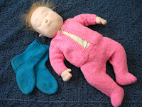 Baby doll wearing knitted outfit next to pair of socks