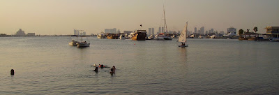 Children play in the sea close to the Doha Sailing Club
