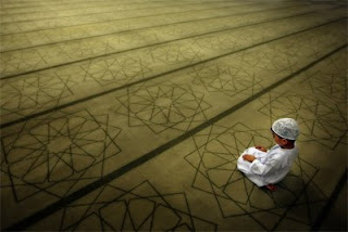 A boy kneels in prayer on the floor of a mosque.