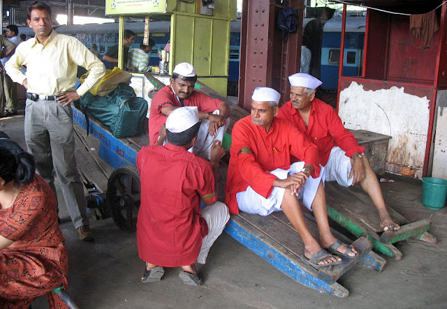 coolies sitting on a hand cart on platform