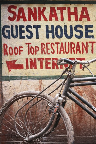 bicycle and guesthouse ads sign in varanasi