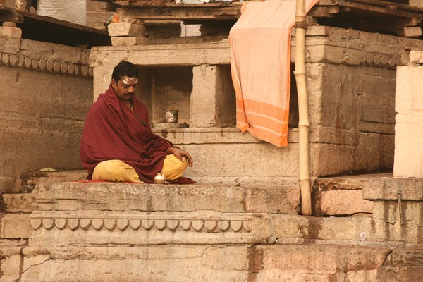 man sits meditating in varanasi