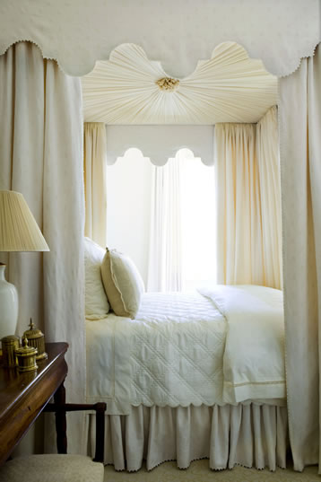White bedroom with an elegant canopy bed