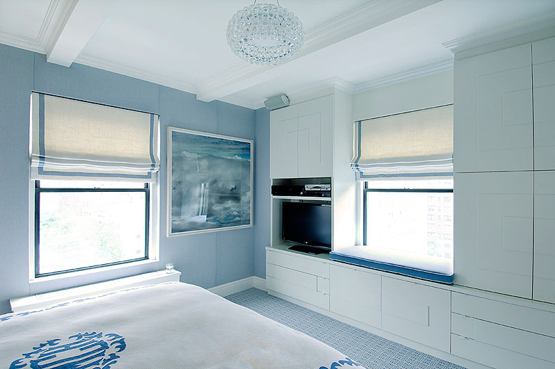Light blue master bedroom with coffered ceiling and a window seat with Roman shades