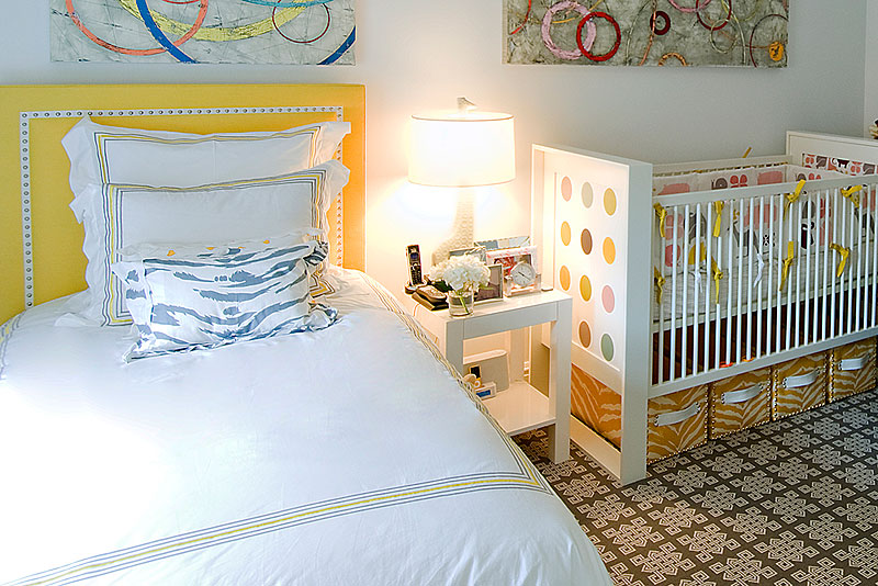 Baby room with crib next to a twin bed with upholstered yellow headboard and graphic print rug