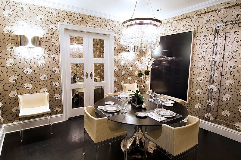 Dining room with white and tan floral wallpaper, crystal chandelier, and a tulip style table with a metal and lucite base and upholstered Philippe Starck Madeline chairs