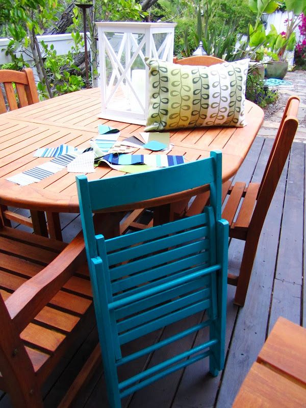 Teak outdoor dining set and a bright blue folding chair