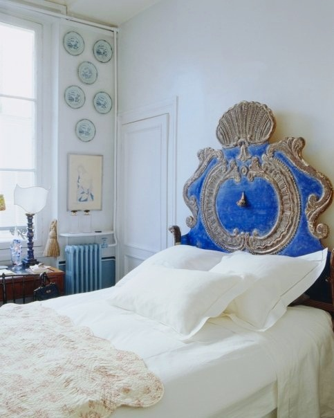 White bedroom in a Paris Apartment with decorative plates on the wall and an 18 century metal and blue Venetian headboard