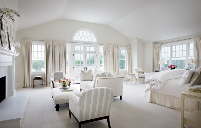 White bedroom with french doors, large windows, a fireplace, sofa, grey and white striped dueling armchairs and an upholstered ottoman