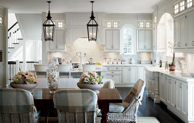 White kitchen with black lantern lights, wood floor, and a wood table surrounded by white wicker chairs with grey gingham covers
