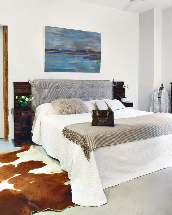 Bedroom with animal skin rug, tufted grey headboard, above the headboard is a painting of a lake, white bedding with a throw at the foot of the bed, and tall nightstands