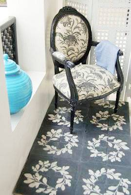 Black and white cement Moroccan tiles with a laurel crown print. On top of them is a black Louis XIV chair