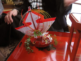 Special pot of New Year's sacred sake, decorated to please the gods with shiny wire sculpture, folded papers representing prayers and money, and ferns representing the fact that the petitioners have nothing to hide.