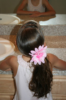 """Back view of young girl outside modeling """"Knots into Side Ponytail"""" hairstyle styled with floral hair accessory"""