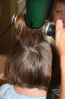 Back view of young girl's hair being styled with a blow dryer and round brush