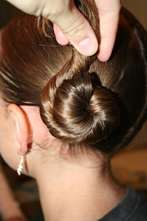 """Side view of young girl's hair being styled into """"Basic Twisty Buns"""" hairstyle"""