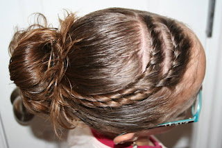 "Top view of young girl modeling ""Hair Twists into Messy Buns"" hairstyle"