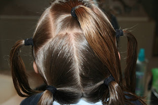 "Back view of young girl's hair being styled into ""Holiday Twisty Buns"" hairstyle"