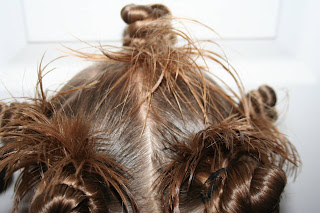 "Close up Back view of young girl modeling ""Holiday Twisty Buns"" hairstyle"