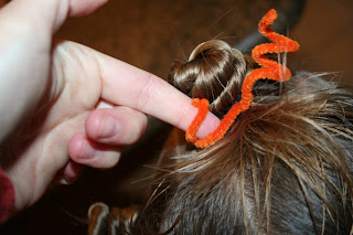 "Close up view of young girl's hair being styled into ""Holiday Twisty Buns"" hairstyle with an orange pipe cleaner"