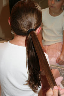 "Back view of young girl's hair being styled into ""Teen Hair Bun"" hairstyle"