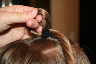 "Close up view of young girl's hair being styled into ""Top-Knot with Banded"" Ponytail"