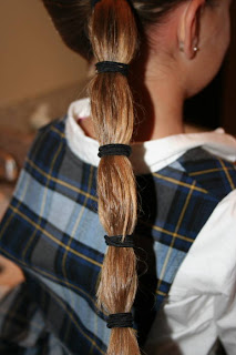 "Back view of young girl's hair being styled into ""Top-Knot with Banded"" Ponytail"