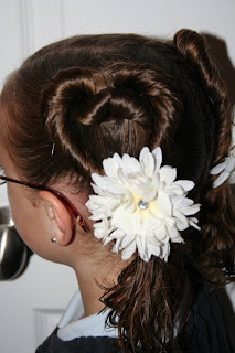 """Side view of a young girl outside modeling """"Two Hearts Twist"""" hairstyle"""