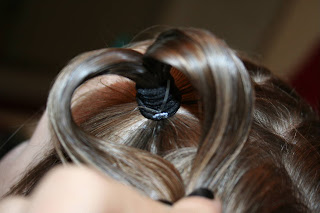 "Close up view of a young girl's hair being styled into ""Heart Pigtail"" hairstyle"