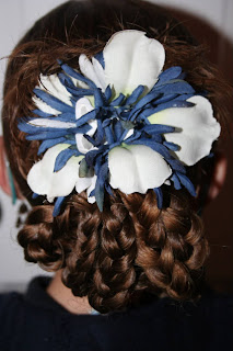 "Back view of young girl modeling ""bundled braids"" hairstyle styled with floral hair accessories"