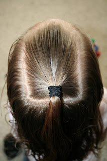 """Top view of young girl's hair being styled into """"The Bun-Hawk"""" hairstyle"""