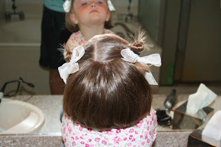 """Back view of young girl modeling """"twisty buns"""" hairstyle"""